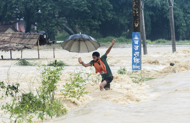A Nepalese man looses his balance while crossing a flooded street in Birgunj, Nepal, Sunday, August 13, 2017. An official said torrential rain, landslides and flooding have killed dozens of people in Nepal over the past three days, washing away hundreds of homes and damaging roads and bridges across the Himalayan country. (Photo by Manish Paudel/AP Photo)