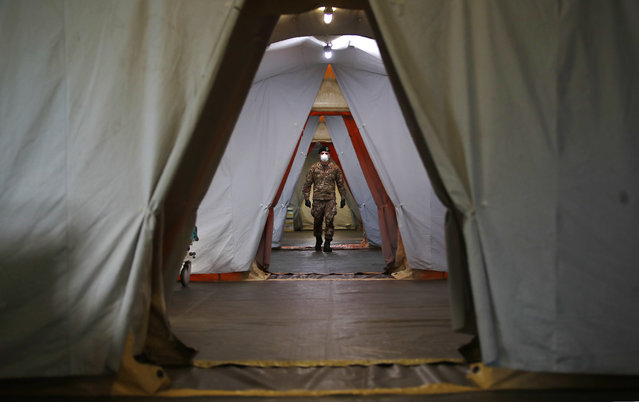 An Italian soldier walks inside the field hospital built in Crema, Italy, Tuesday, March 24, 2020. Cuba has sent a medical brigade to Italy to help treat coronavirus patients in the field hospital that was set up in Crema, one of Northern Italy's areas most hit by the virus. (Photo by Antonio Calanni/AP Photo)