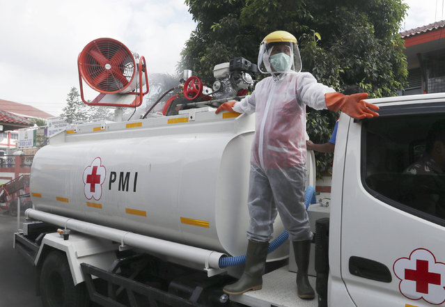 A member of Indonesian Red Cross stand on the back of a truck and spray disinfectant in an attempt to curb the spread of coronavirus outbreak at a neighborhood in Jakarta, Indonesia,Wednesday, April 8, 2020. (Photo by Achmad Ibrahim/AP Photo)