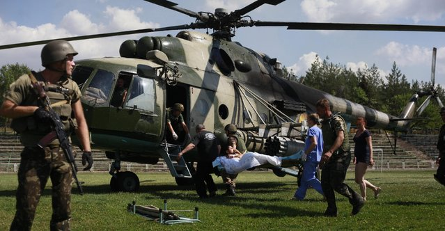Ukrainian soldiers evacuate a wounded comrade close to Luhansk, eastern Ukraine, Thursday, August 21, 2014. The rebel stronghold 20 kilometers from the Russian border has been under siege for 19 days, lacking basic amenities like running water or electricity. (Photo by Petro Zadorozhnyy/AP Photo)
