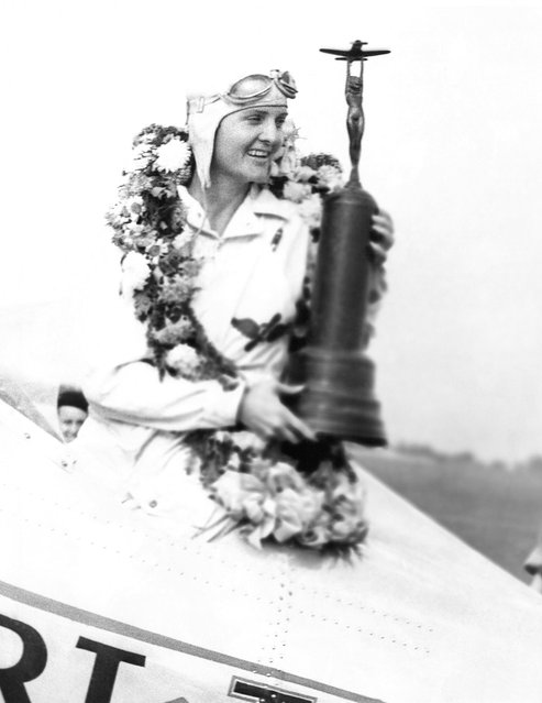 Miss Gladys O'Donnell of Long Beach, Calif., is shown in the cockpit of her plane at the national air races in Cleveland, on September 3, 1937 after she had won the Amelia Earhart memorial race, Miss O'Donnell has the trophy and wreath signifying victory. (Photo by AP Photo)