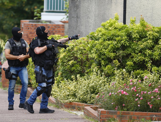 Hooded Police officers conduct a search in Saint-Etienne-du-Rouvray, Normandy, France, following an attack on a church that left a priest dead, Tuesday, July 26, 2016. Two attackers invaded a church Tuesday during morning Mass near the Normandy city of Rouen, killing an 84-year-old priest by slitting his throat and taking hostages before being shot and killed by police, French officials said. (Photo by Francois Mori/AP Photo)