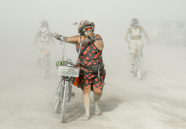 Participants make their way through dust at Burning Man in the Black Rock Desert of Nevada on Wednesday, September 2, 2015. The 29th annual alternative living event is traditionally centered around the ritual burning of a large wooden effigy. (Photo by Andy Barron/The Reno Gazette-Journal via AP Photo)