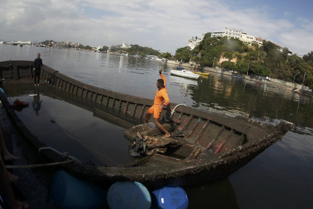 Anderson (R) and Leandro inspect the boat they were hired to refloat under contract for its owner from the bottom of Guanabara Bay in Rio de Janeiro, Brazil, July 31, 2016. Anderson and Leandro salvage sunken boats from the bottom of the notoriously polluted bay part of which will host the Olympic windsurfing and sailing competitions. (Photo by Ricardo Moraes/Reuters)
