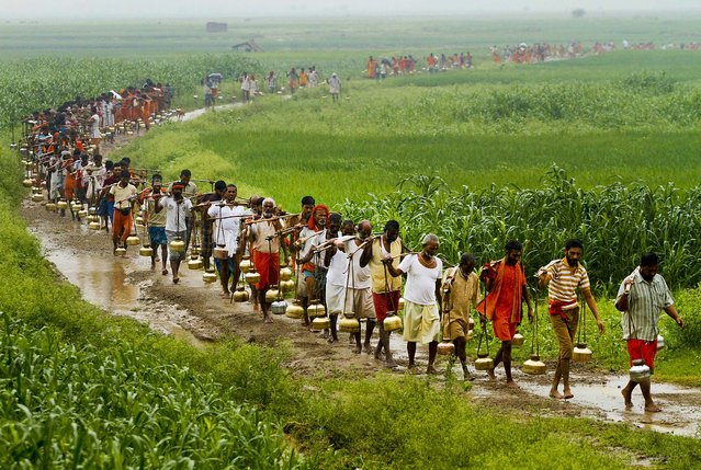"""Hindus carrying metal pots filled with water from the River Ganges, walk to a Lord Shiva temple to perform a ritual during """"Malmas"""" in Allahabad, India, on September 16, 2012. """"Malmas"""" is an extra lunar month according to the Hindu calendar that occurs once in three years and is considered auspicious for Shiva worship. (Photo by Rajesh Kumar Singh/Associated Press)"""