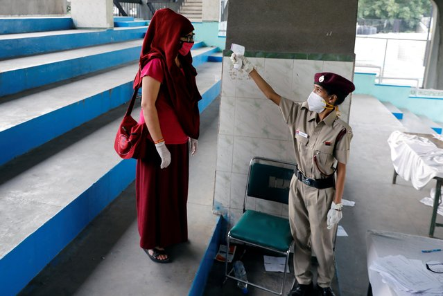 A stranded resident of Ladakh, a union territory in India, is thermal screened before being seated in buses which will take them back to Ladakh, after few restrictions were lifted by Delhi government during an extended nationwide lockdown to slow the spread of the coronavirus disease (COVID-19), in New Delhi, India, May 11, 2020. (Photo by Anushree Fadnavis/Reuters)