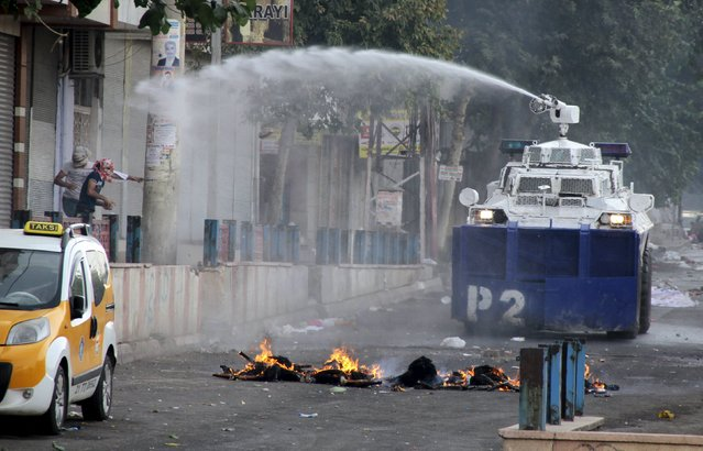 Riot police use a water cannon to disperse protesters in the Kurdish-dominated southeastern city of Diyarbakir, Turkey, September 13, 2015. (Photo by Sertac Kayar/Reuters)