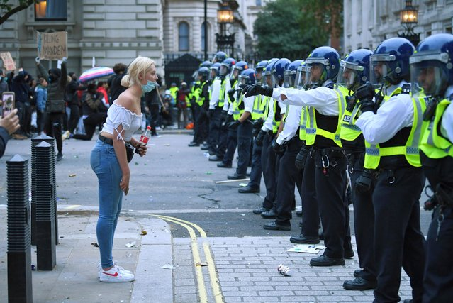A woman stands in front of police officers during a Black Lives Matter protest in London, following the death of George Floyd who died in police custody in Minneapolis, London, Britain, June 7, 2020. (Photo by Dylan Martinez/Reuters)