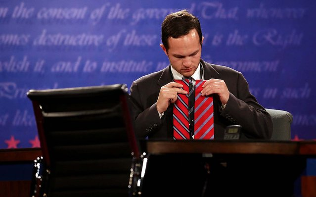A Romney assistant tests ties under the stage lighting for television before the debate; Romney wound up wearing the tie on the right. (Photo by Richard Graulich/The Palm Beach Post)