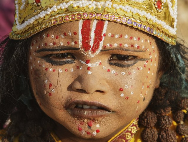 A girl dressed as a Hindu Goddess sits on the banks of river Ganga during the Navratri festival in the northern Indian city of Allahabad October 16, 2012. Devotees worship various forms of Hindu goddesses during the festival, whose name literally means nine nights. (Photo by Jitendra Prakash/Reuters)