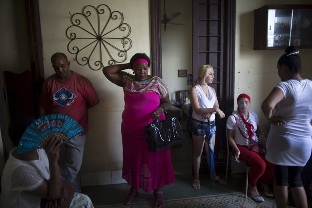 People prepare to take part into a ceremony of the Afro-Cuban religion Santeria to attract spirits of dead ancestors to ask for guidance in downtown Havana, August 18, 2015. (Photo by Alexandre Meneghini/Reuters)