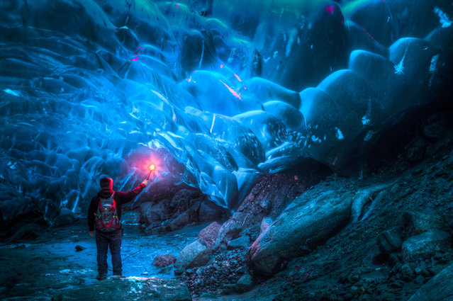 A friend of Ron Gile holding up a red road flare inside the amazing Alaskan ice cave. (Photo by Ron Gile/Caters News)