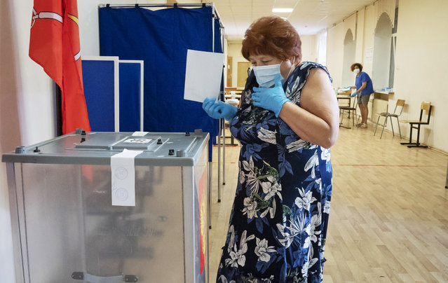 A voter wearing a face mask and protective gloves to protect against coronavirus walks to cast her ballot at a polling station in St.Petersburg, Russia, Thursday, June 25, 2020. Polls have opened in Russia on Thursday for a week-long vote on a constitutional reform that may allow President Vladimir Putin to stay in power until 2036. (Photo by Dmitri Lovetsky/AP Photo)