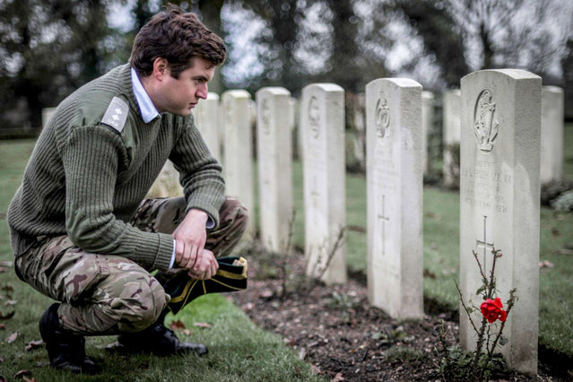 Lt Lane reading a grave stone inscription of a Kings Royal Irish Hussars soldier at a cemetery in Normandy; Army Photographic Competition, Britain, October 8, 2014. (Photo by MoD/Geoff Robinson Photography/REX Features)