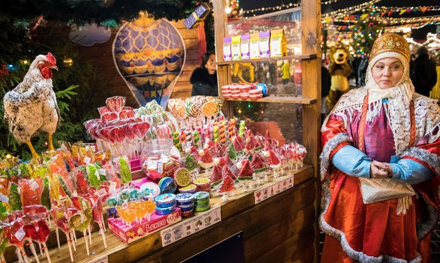 A vendor wearing a traditional dress sells sweets at a Christmas market in Red Square in Moscow on December 4, 2017. (Photo by Mladen Antonov/AFP Photo)