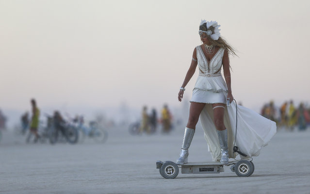 A woman rides an electric scooter during the Burning Man festival in the Black Rock Desert, Nevada on September 1, 2016. (Photo by Chase Stevens/AP Photo)