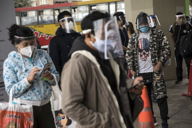 Commuters wearing protective face masks and face shields wait to enter a train station in Lima, Peru, Saturday, July 25, 2020. Peru ordered the mandatory wearing of protective face masks and shields on public transportation amid the new coronavirus pandemic.(Photo by Rodrigo Abd/AP Photo)