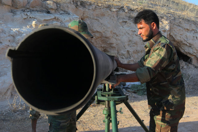 Free Syrian Army fighters prepare to fire a Grad rocket from Halfaya town in Hama province, towards forces loyal to Syria's President Bashar al-Assad stationed in Zein al-Abidin mountain, Syria September 4, 2016. (Photo by Ammar Abdullah/Reuters)