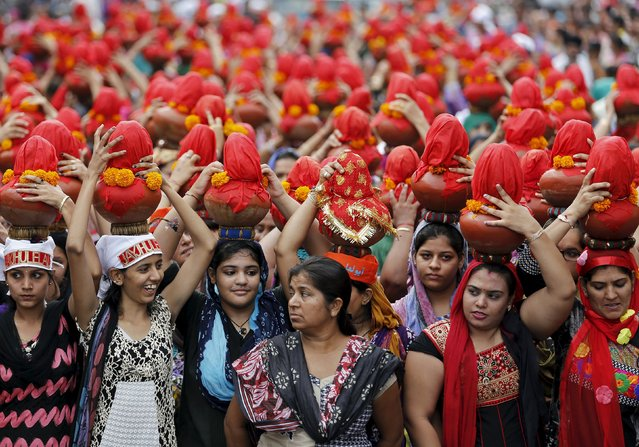 Devotees carry earthen water pots as they take part in a Jhulelal Chaliha procession in Ahmedabad, India, September 19, 2015. Jhulelal Chaliha, a 40-day-long fasting festival of the Sindhi community, ended on Saturday with a colourful procession of earthen pots carried by hundreds of male and female devotees on their heads for what they say to be the betterment of their family and society. (Photo by Amit Dave/Reuters)