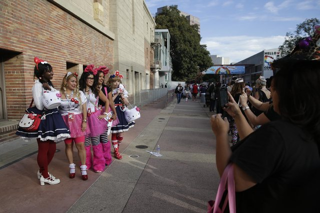 Fans and models pose for photos while waiting line for the Hello Kitty Con, the first-ever Hello Kitty fan convention, held at the Geffen Contemporary at MOCA Thursday, October 30, 2014, in Los Angeles. (Photo by Jae C. Hong/AP Photo)