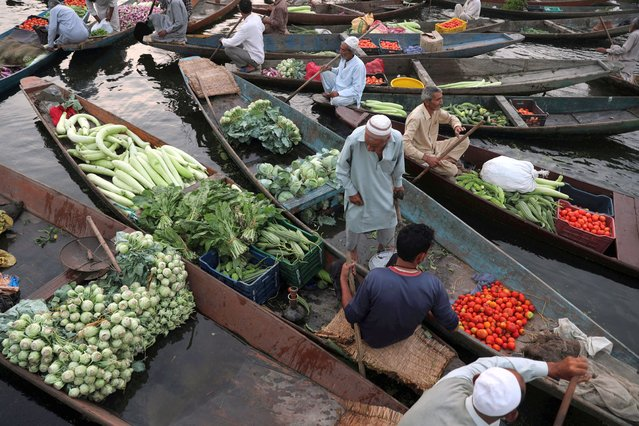 People attend a floating vegetable market on Dal Lake in Srinagar, Jammu and Kashmir, India, 29 July 2020. People gather every morning to purchase or sell their vegetables at the floating market on the Dal Lake, which is home to floating gardens that produce vegetables in all four seasons of the year. (Photo by Farooq Khan/EPA/EFE)