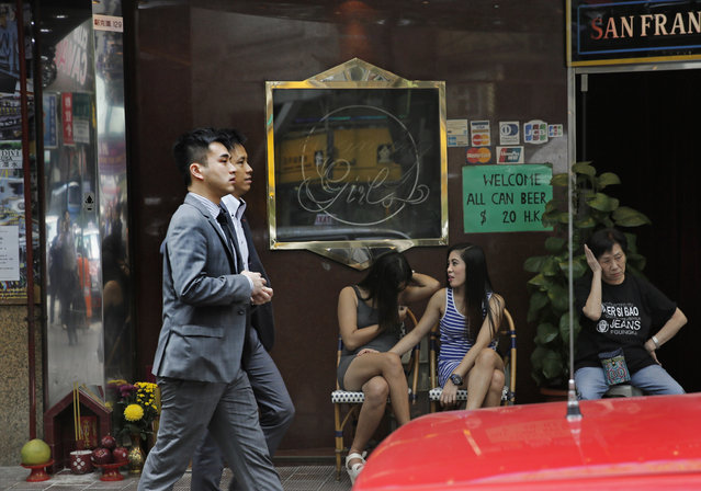Bar girls sit outside a night club in Hong Kong's Wan Chai district Wednesday, November 5, 2014. For generations of Western men, Hong Kong's Wan Chai neighborhood captured all the mystery and hedonism of this financial capital known around the world as the Pearl of the Orient. (Photo by Vincent Yu/AP Photo)
