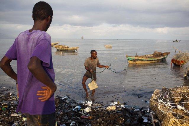 A fisherman brings his boat ashore as a precaution against Hurricane Irma, in the seaside slum of Port-au-Prince, Haiti, Wednesday, September 6, 2017. (Photo by Dieu Nalio Chery/AP Photo)