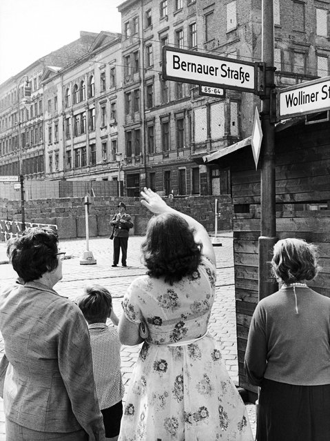 The August 13, 1962 file photo shows West Berliners waving to relatives in East Berlin one year after the Berlin Wall was erected at Bernauer Strasse in Berlin. (Photo by Werner Kreusch/AP Photo)