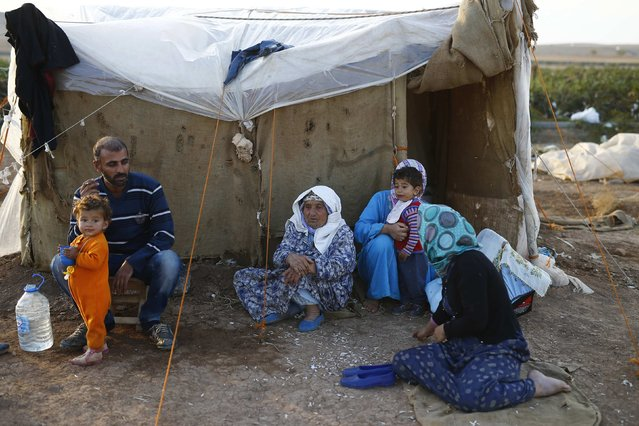Kurdish refugees from the Syrian town of Kobani sit near a makeshift tent in a camp in the southeastern town of Suruc, Sanliurfa province in this October 25, 2014 file photo. (Photo by Kai Pfaffenbach/Reuters)