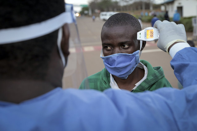 A Burundian refugee from Mahama camp in Rwanda is checked for fever as a precaution against the spread of the coronavirus after arriving back in Gasenyi, Burundi, Thursday, August 27, 2020. Nearly 500 Burundian refugees living in Rwanda began their journey back to their home country Thursday, the first group to return from Rwanda after five years in exile following deadly political violence that sent many fleeing. (Photo by Berthier Mugiraneza/AP Photo)