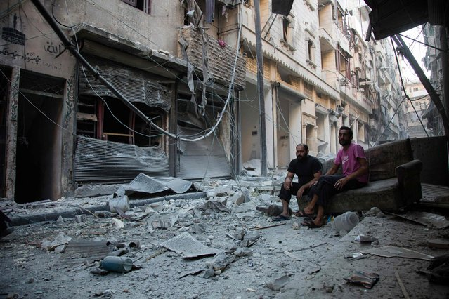 Syrians sit and look at the rubble following an airstrike on the regime-controlled neighbourdhood of Karm al-Jabal on September 18, 2016. Syria's ceasefire was on the brink of collapsing Sunday, after a US-led coalition strike killed dozens of regime soldiers and Aleppo city was hit by its first raids in nearly a week. (Photo by Karam Al-Masri/AFP Photo)