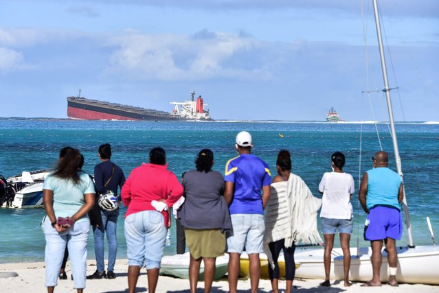 Bystanders look at MV Wakashio bulk carrier that had run aground and from which oil is leaking near Blue Bay Marine Park in south-east Mauritius on August 6, 2020. The carrier, belonging to a Japanese company but Panamanian-flagged, ran aground on July 25 and its crew was evacuated safely. The ship was empty at the time but was carrying 200 tonnes of diesel and 3,800 tonnes of bunker fuel, according to the local press. (Photo by Dev Ramkhelawon/L'Express Maurice/AFP Photo)