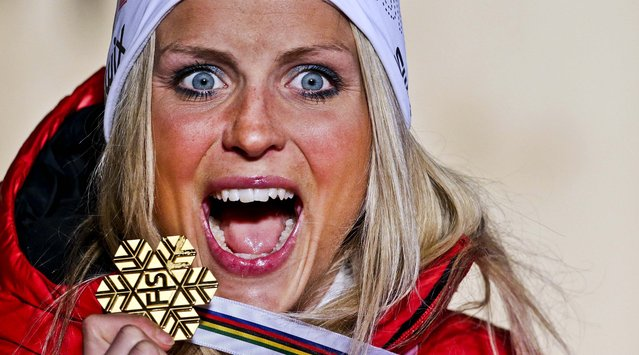 Winner Therese Johaug of Norway celebrates on the podium during the medal ceremony after the women's 10 km Free Individual competition of the Nordic Ski World Championships in Val di Fiemme, Italy, on February 26, 2013. (Photo by Matthias Schrader/Associated Press)