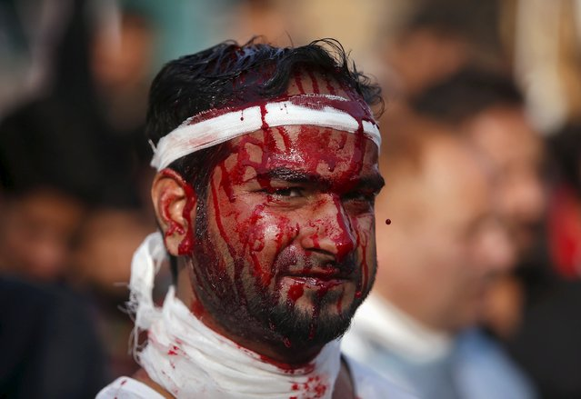A Shi'ite Muslim mourner looks on after flagellating himself during a Muharram procession ahead of Ashura in Srinagar, October 23, 2015. Ashura, which falls on the 10th day of the Islamic month of Muharram, commemorates the death of Imam Hussein, grandson of Prophet Mohammad, who was killed in the 7th century battle of Kerbala. (Photo by Danish Ismail/Reuters)