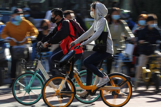People wearing face masks to help curb the spread of the coronavirus ride bicycle during the morning rush hour in Beijing, Monday, October 12, 2020. Even as China has largely controlled the outbreak, the coronavirus is still surging across the globe with ever rising death toll. (Photo by Andy Wong/AP Photo)