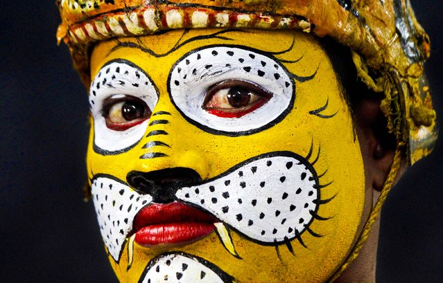 A traditional tiger dancer waits to perform during a Save Our Tigers awareness campaign in Kolkata, India, on March 21, 2013. India's latest tiger census counted at least 1,706 tigers in forests across the country. As many as 100,000 tigers are thought to have roamed India a 100 years ago. (Photo by Bikas Das/Associated Press)