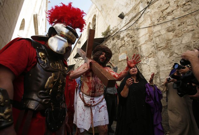 A man playing the role of Jesus carries a cross to the Church of the Holy Sepulchre on Good Friday during Holy Week, in Jerusalem's Old City March 29, 2013. Christian worshippers retraced the route Jesus took along Via Dolorosa to his crucifixion in the Church of the Holy Sepulchre. Holy Week is celebrated in many Christian traditions during the week before Easter. (Photo by Baz Ratner/Reuters)