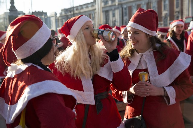 Participants dressed in Santa costumes drink alcoholic beverages during the annual SantaCon event in London December 6, 2014. (Photo by Neil Hall/Reuters)