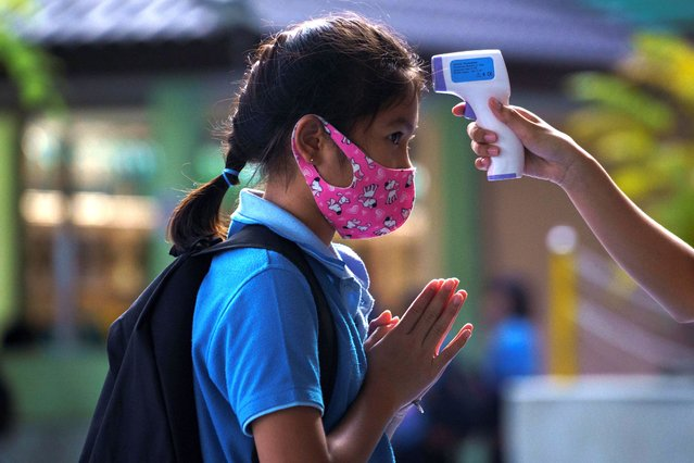 A student wearing a face mask has her body temperature checked due to the spread of the coronavirus disease (COVID-19) before entering a school in Bangkok, Thailand, October 7, 2020. (Photo by Athit Perawongmetha/Reuters)