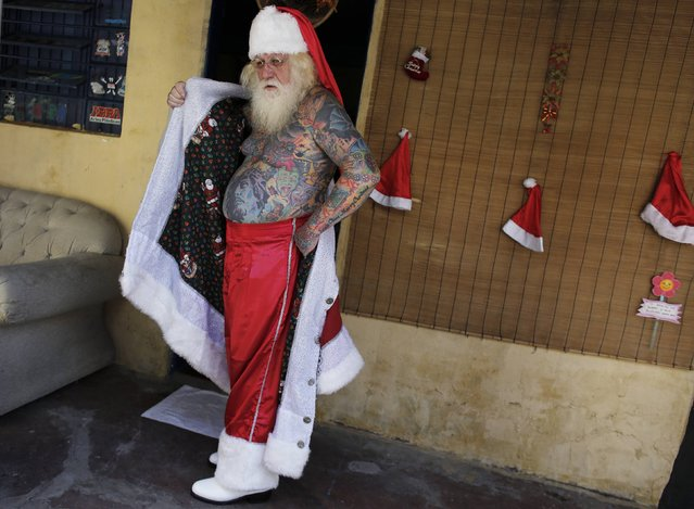 Vitor Martins poses as he puts on his Santa outfit inside his house, before a performance with children in Sao Caetano do Sul's town square, near Sao Paulo, December 7, 2014. (Photo by Nacho Doce/Reuters)