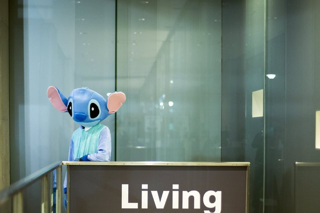 A person dressed up as Disney character Stitch stands outside a shopping centre during Halloween celebrations in the Shibuya district in Tokyo, Japan October 31, 2015. (Photo by Thomas Peter/Reuters)