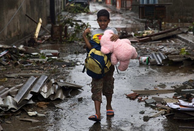 A boy walks, carrying a backpack and a teddy bear, through a street littered with debris the morning after Hurricane Matthew drove across Baracoa, Cuba, Wednesday, October 5, 2016. (Photo by Ramon Espinosa/AP Photo)