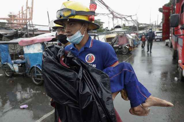 A rescuer carries a sick child as they evacuate residents living along a coastal community in Manila, Philippines on Sunday, November 1, 2020. (Photo by Aaron Favila/AP Photo)