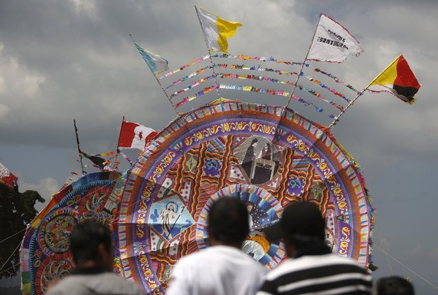 People stand in front of giant kites in the cemetery of Santiago Sacatepequez, Guatemala, November 1, 2015. (Photo by Jorge Dan Lopez/Reuters)