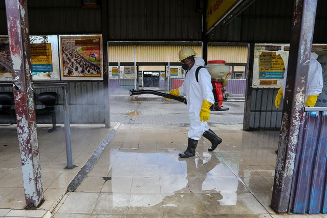 A municipal worker sprays disinfectant at the central bus terminal amid the coronavirus pandemic in Colombo, Sri Lanka, 26 October 2020. Sri Lankan government implement a curfew in some parts of the country due to a sudden spike of the Covid-19 cluster from a fish market in Colombo. (Photo by Chamila Karunarathne/EPA/EFE)