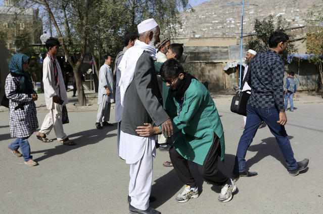In this Sunday, October 9, 2016. photo, an Afghan security person checks a man during a commemoration of Ashoura in Kabul, Afghanistan. (Photo by Rahmat Gul/AP Photo)