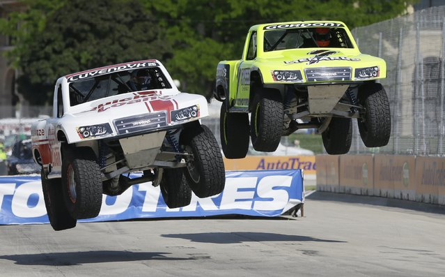 Arie Luyendyk Jr., left, and Robby Gordon jump off a ramp during the SPEED Energy Stadium Super Truck Series auto race in Detroit, Friday, May 30, 2014. (Photo by Carlos Osorio/AP Photo)