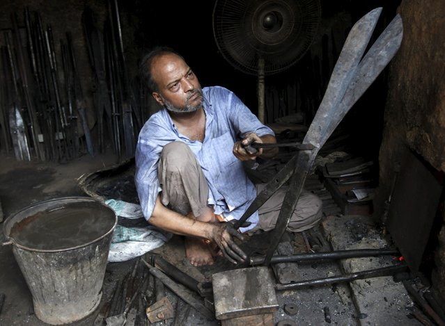 A blacksmith checks the blades alignment of a pair of scissors after shaping them at a workshop in Karachi, Pakistan, October 10, 2015. (Photo by Akhtar Soomro/Reuters)