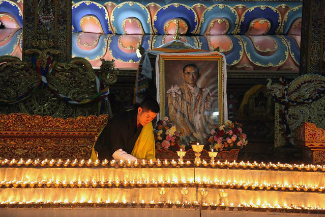 This photograph released on October 13, 2016 by Bhutan's Royal Office for Media on Bhutanese King Jigme Khesar's Facebook page shows King Jigme Khesar at the Kuenra of the Tashichhodzong in Thimpu lighting candles next to a portrait of Thailand's King Bhumibol Adulyadej, who died in Bangkok. Thailand's King Bhumibol Adulyadej has died after a long illness, the palace announced on October 13, ending a remarkable seven-decade reign and leaving a divided people bereft of a towering and rare figure of unity. (Photo by AFP Photo/Royal Office for Media Bhutan)