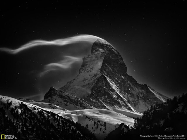 """Winner, Professional Landscape. A Portrait of the Matterhorn. When I was young, I had long fantasized about climbing the Matterhorn but I never really had the chance. The Matterhorn was the last great Alpine peak to be conquered and its first ascent in 1865 marked the end of the golden age of alpinism. Its North Face, which is on all images, is amongst the """"Three Great Problems"""" in the Alps and was not climbed until 1931. I have been around Zermatt countless times, the village nestled at the foot of the Matterhorn, looking toward the mountains and trying to capture the exquisiteness of this magical peak and its endless state of change; to compress the passing of time the beauty of the wind and the clouds dancing around the mountain. This portfolio is a kind of memento to all climbers who dared to go there and for those who never returned. Night Clouds #3, 07 Jan 2012 – 3:17 AM – Matterhorn at full moon. (Photo by Nenad Saljic/2013 Sony World Photography Awards)"""
